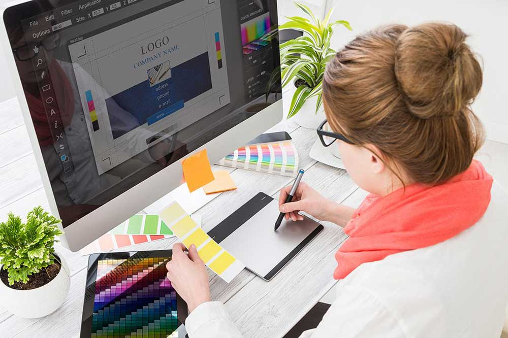 Graphic designer drawing on graphics tablet at workplace