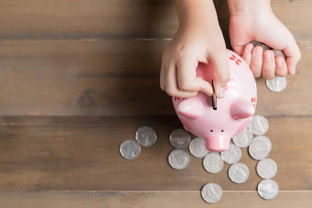 kid put coin to piggy bank on the vintage wood background