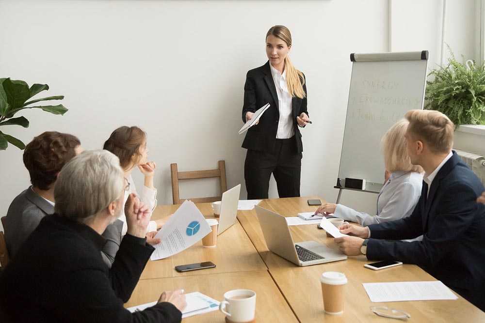 Businesswoman talking to business team answering questions at group meeting